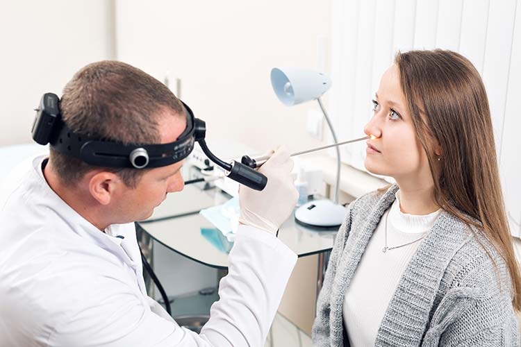 ear nose throat doctor examining a patient